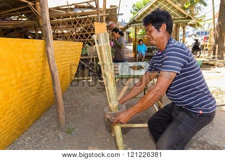 TRANG, THAILAND, JANUARY 11, 2016 : Craftsman splitting a bamboo with a special tools for building a wooden table in Trang, Thailand