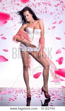 Gorgeous glamour girl with a long voile over rose petals
