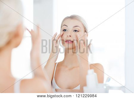 beauty, skin care and people concept - smiling young woman applying cream to face and looking to mirror at home bathroom