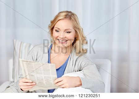 news, press, media, leisure and people concept - smiling woman reading newspaper at home