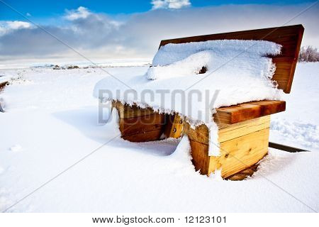 A snow covered bench in a snowy large field with a blue sky and some clouds