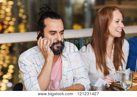 leisure, technology, lifestyle and people concept - man with smartphone and friends dining at restaurant