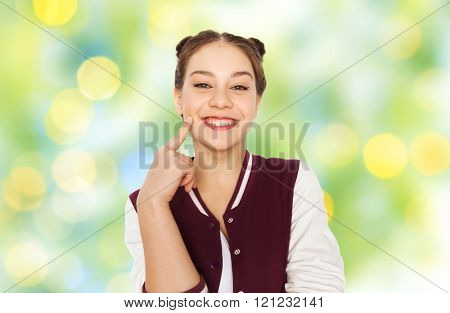 people and teens concept - happy smiling pretty teenage girl with eye makeup over green summer holidays lights background