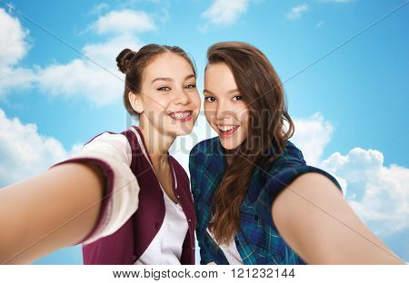 people, friends, teens and friendship concept - happy smiling pretty teenage girls taking selfie over blue sky and clouds background