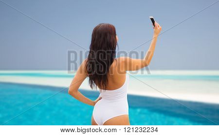 summer, travel, technology and people concept - sexy young woman taking selfie with smartphone over beach and swimming pool background