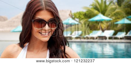 summer vacation, tourism, travel, holidays and people concept -face of smiling young woman with sunglasses over beach and swimming pool background