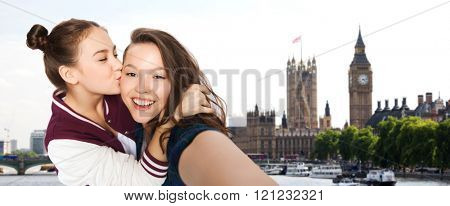 people, travel, tourism and friendship concept - happy smiling pretty teenage girls taking selfie and kissing over london background