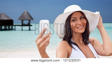 travel, summer, technology and people concept - sexy young woman taking selfie with smartphone over bungalow on beach background