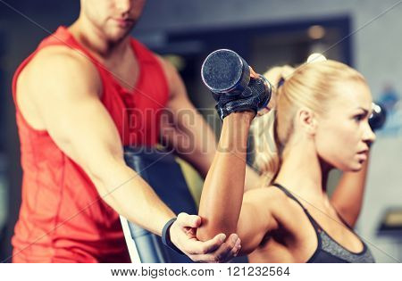 sport, fitness, bodybuilding, lifestyle and people concept - man and woman with dumbbells flexing muscles in gym poster