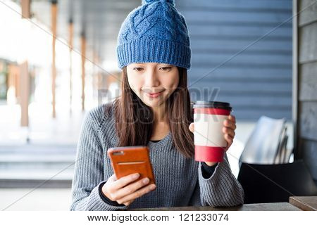 Woman look at cellphone at outdoor cafe