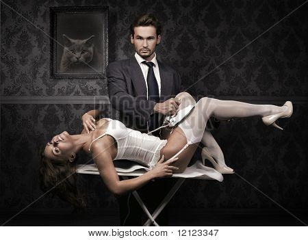 Handsome man ironing attractive brunette