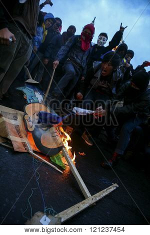 Quito, Ecuador - August 27, 2015: Angry group of poeple burning polititcal signs on the ground