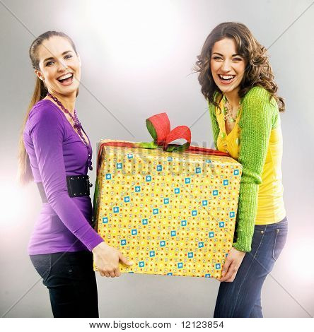portrait of two happy beautiful girls holding a present