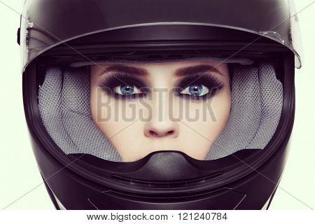 Vintage style close-up portrait of young beautiful woman with stylish make-up in biker helmet