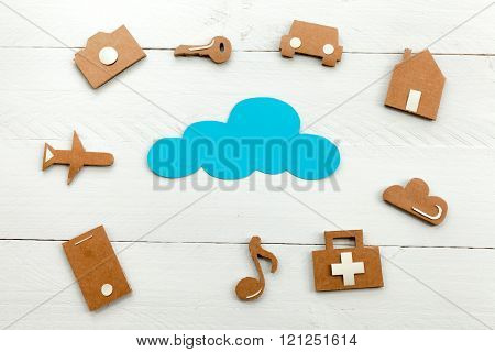 Cardboard web icons  and blue cloud on blue background