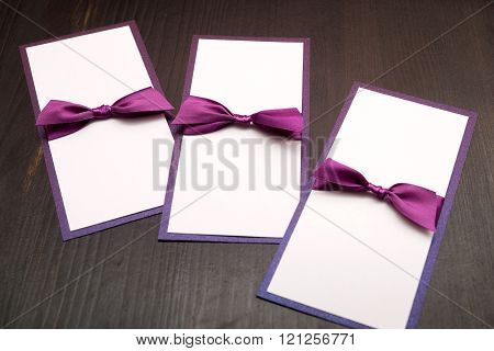 Handmade Cards With Purple Satin Tape On Wood Background