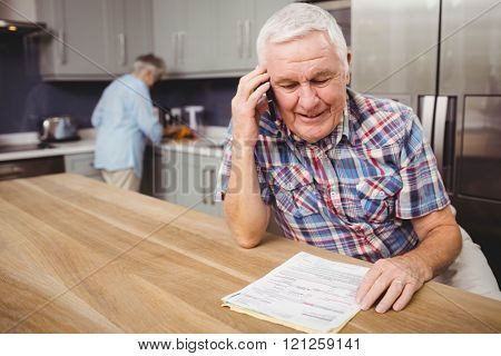 Senior man talking on phone and woman working in kitchen at home