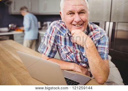 Portrait of happy senior man using laptop and woman working in kitchen at home