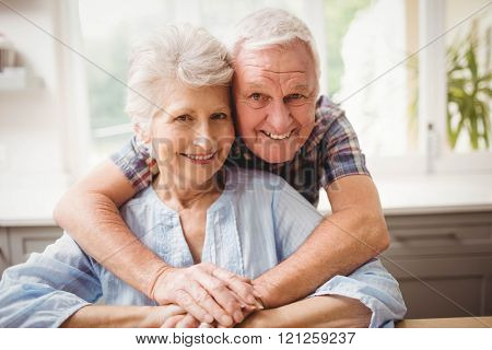 Portrait of senior couple embracing at home poster