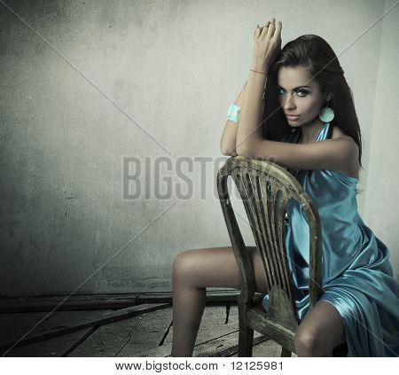 Splendida bellezza bruna seduta su una sedia