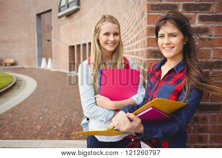 Smiling students reading book at university