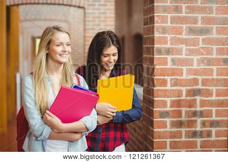 Smiling students with books in the hallway at university