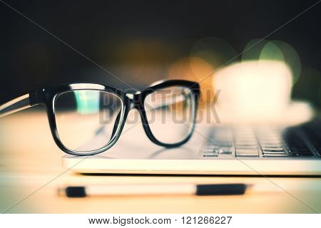 Eyeglasses On Laptop With Pen On Wooden Table, Close Up