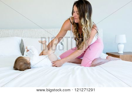 cute baby is trying to roll over on a bed while a brunette woman holds her