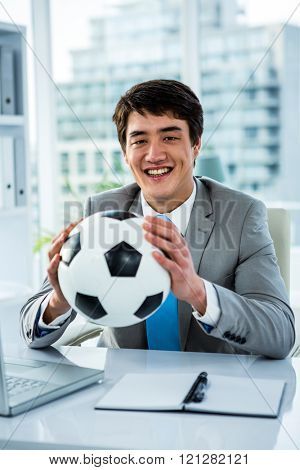 Asian businessman holding soccer ball with thumps up in office