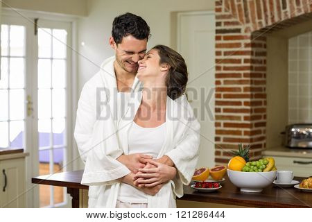 Couple in bathrobe rubbing their nose while embracing each other in kitchen