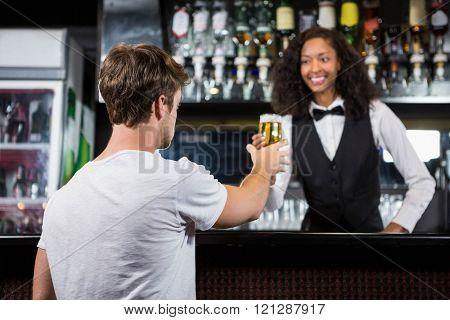 Barmaid serving beer to man at bar counter in bar