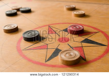 A Game Of Carrom With Scattered Stones On The Board Around The Center Star