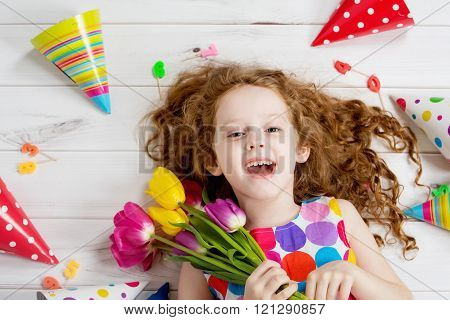 Happy laughing girl in birthday party lying on wooden floor.