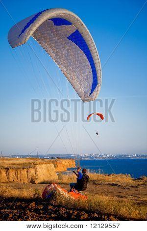 Two paragliders in sky above sea coastline