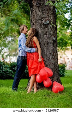Young couple kissing in green park near tree