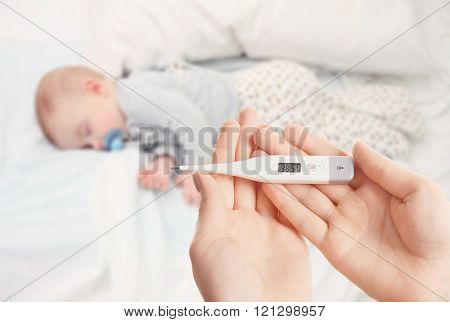Loving baby sleeping on soft bed and hand with thermometer