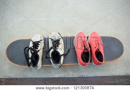 closeup of sneakers on skateboard at skatepark ramp