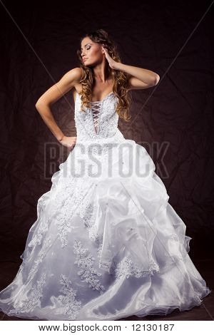 Fashion model wearing wedding dress at brown studio background poster