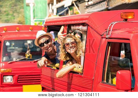 Cheerful Tourist Couple In Tuk Tuk Thai Taxi With Pointing Finger -