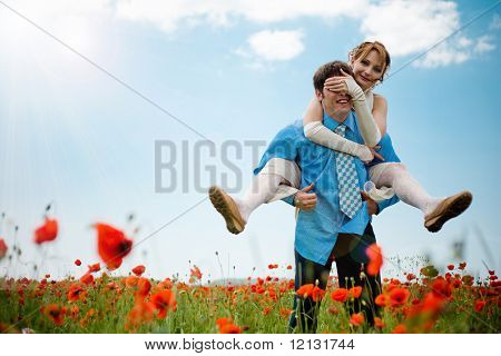 Wedding couple playing at poppy field outdoors on blue sky background