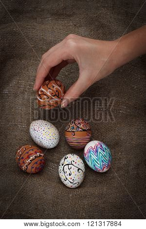 Colorful Easter Eggs On Burlap, Female Hand Chose And Pick One