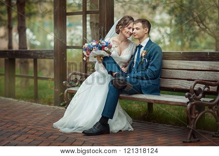 Newlyweds Sitting On A Bench