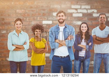 Group portrait of happy young colleagues against brick wall