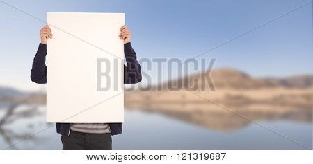 Man showing billboard in front of face against lake