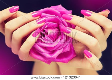 Manicured hands with bright pink nail Polish on the nails .
