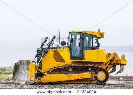 dirty Yellow bulldozer going left on ground