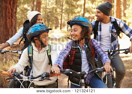 African American Family Cycling Through Fall Woodland