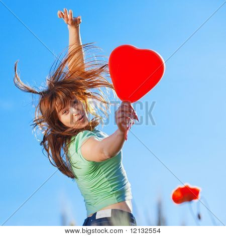 Jumping teenage girl with a heart