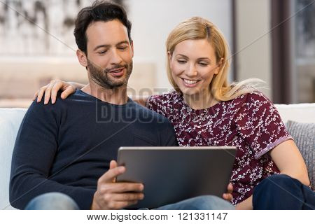 Couple sitting on couch and using digital tablet. Happy friends watching social media on laptop sitting on couch. Smiling young couple using a laptop in their living room.