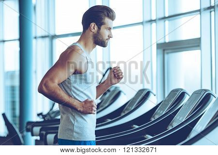 Running fast. Side view of young man in sportswear running on treadmill at gym